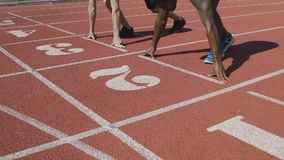 Two sports men at starting position preparing for run, university competition. Stock footage stock video