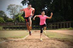 Two sports partners are jogging together on a sunny day wearing orange and pink shirts. They look at each other and smile, enjoy stock photo