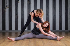 Two sports woman. Fitness instructor. Lesson with a trainer. Two women doing stretching back to help complete the royalty free stock images