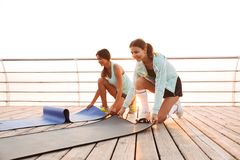 Two sports women friends outdoors on the beach with carpet. stock image