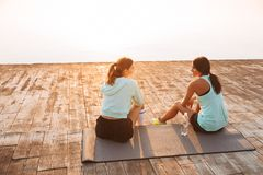Two sports women friends outdoors on the beach sitting talking with each other stock photography