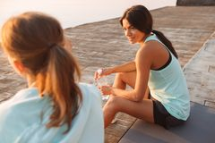 Two sports women friends outdoors on the beach sitting talking with each other royalty free stock photography