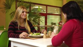 Two sports women sit in a fitness club restaurant and chat during a snack stock video