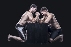 Two sportsmen armwrestling. Two armwrestlers, have an arm wrestling match on a black box shirtless Stock Image