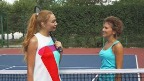 Two girls greeting on a tennis court. Two sportsmen come to a net in order to shake hands and have a short talk. They smiling. One of them has a racket. They are stock video