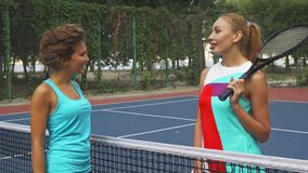 Two girls shaking hands before playing tennis. Two sportsmen come to a net in order to shake hands and wish good luck. They are going to play. One girl holding a stock footage