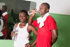 Two sportsmen drinking mineral water. Young women and her coach drink water from the gym Royalty Free Stock Images