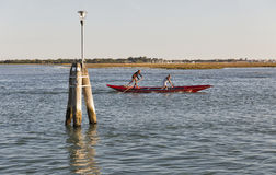 Two sportsmen rowing a gondola in Venice lagoon, Italy. Royalty Free Stock Photography