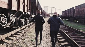 Male athletes running on railroad. Two sportsmen running on railroad along trains stock video