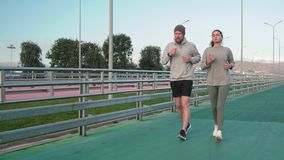 Young guy and girl are running on stadium and chatting during workout. Two sportspersons are jogging on training session on open stadium track. Man and woman are stock video