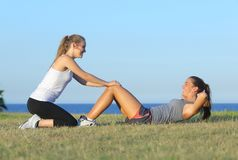 Two sportswomen doing crunches. On the grass with the sea in the background Stock Photos