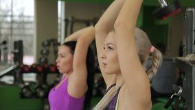 Two sportswomen are doing seated triceps dumbbell press in modern gym. Female athlets are concentrated on the power exercises. Blond lady is wearing dark top stock video
