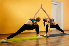 Two sportswomen doing stretching exercises. In gym Stock Photography
