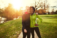 Two sportswomen in park hugging and looking at camera Royalty Free Stock Photos