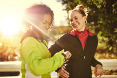 Two sportswomen in park, smiling and looking at watch. Royalty Free Stock Photos