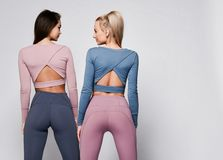 Free Two Sporty Blonde And Brunette Girls In Athletic Body Cloth Sport Wear Cloth Stand Together After Workout On Gray Royalty Free Stock Photo - 147842385
