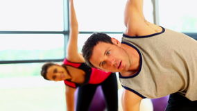 Two sporty friend stretching their bodies. In fitness hall stock video