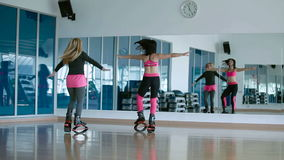 Two sporty girls dancing and jumping with the kangoo shoes stock video