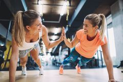 Two sporty girls doing push ups in gym. Together stock photo