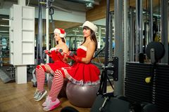 Two sporty girls in Santa Claus costumes at the gym in Christmas Stock Image