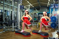 Two sporty girls in Santa Claus costumes at the gym in Christmas. And New Years Stock Photo