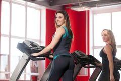 Two sporty girls walk on treadmill Stock Image