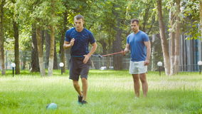 Two sporty man or instructors doing gymnastic exercise outdoor.  stock footage