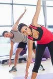 Two sporty people stretching hands at yoga class Royalty Free Stock Image