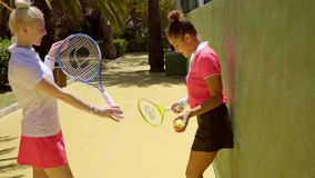 Two sporty sexy young woman tennis players. Standing leaning against a wall in the sunshine chatting after a game stock video footage