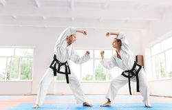 Two sporty woman fighting at karate training in martial arts school. stock photo