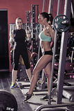 Two sporty woman workout in the gym. Picture of young women making exercise at the gym stock photography