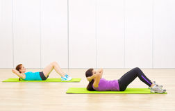Two sporty women at fitness club Royalty Free Stock Photos