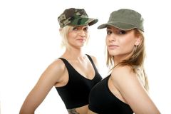 Two sporty women in military caps Royalty Free Stock Images