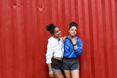 Two sporty women posing near red wall. After workout Royalty Free Stock Photos
