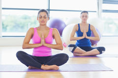 Two sporty women sitting with joined hands at fitness studio Royalty Free Stock Image