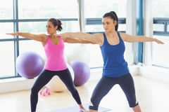 Two sporty women stretching hands at yoga class Stock Photo