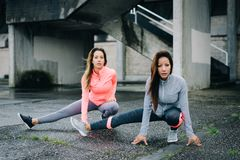 Two urban fitness women stretching legs outside stock photo