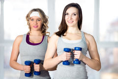 Two sporty young females doing side bends with dumbbells Royalty Free Stock Images