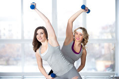 Two sporty young females having aerobics practice with dumbbells Royalty Free Stock Photo
