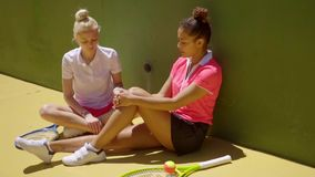 Two sporty young tennis friends sitting relaxing. In the sun leaning against a wall on the court chatting stock footage