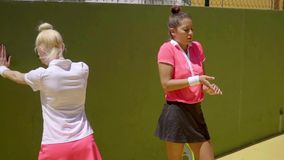 Two sporty young tennis players warming up. Two sporty young female tennis players warming up together doing stretching exercises before a match stock footage