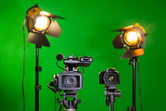Two spotlights with Fresnel lenses, camcorder and SLR camera on a green background. Shooting in the interior with artificial light Stock Photos