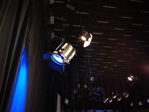 Two spotlights - one with a blue filter. Two spotlights on a grid of lights - one with a blue filter in a television studio stock photos