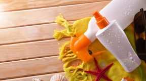Two spray suncream lying with shells on wooden slats top Royalty Free Stock Photos