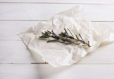 Two sprigs of rosemary on paper on white wooden background. The Two sprigs of rosemary on bakery paper on white wooden background Royalty Free Stock Photos