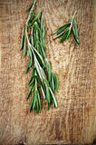 Two sprigs of rosemary on a wooden board top view Royalty Free Stock Photos