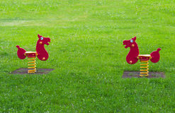 Two spring horse toy surrounded by grass in a playground Stock Images