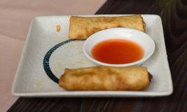 Two spring rolls on a greasy plate. With salsa in the middle Stock Images