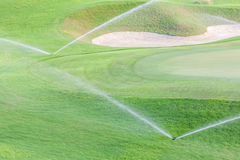 Two sprinklers watering system working in green golf course. Stock Photos