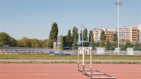 Two sprinters jump over the hurdles at the stadium stock footage